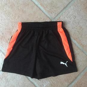 Varetype: Fodboldshorts - håndboldshorts - shorts Størrelse: 128 Farve: Sort Oprindelig købspris: 199 kr.  Striben er mere varm orangerød i virkeligheden, end på billedet.