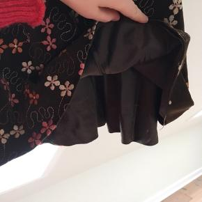 Vintage nederdel fra 1960'erne. Den er kort og lavet i brun velour med broderede blomster på. Den er virkelig velholdt og meget smuk.