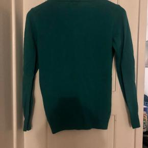 """Lækker blød, grøn cardigan fra Benetton som jeg aldrig rigtigt har fået brugt. Har nok haft den på og vasket den en enkelt gang.   100 % virgin wool. Der står """"merino extra fine Italian yarn"""" på mærket i nakken.   Farven er svær at fange, men den er lidt mere grøn end på billede 1+2."""