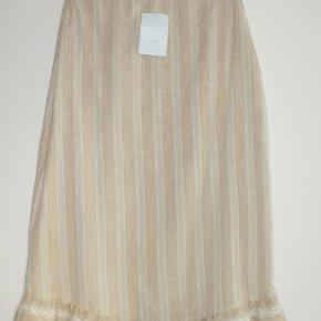 Skønt sæt: Bluse og nederdel, som kan bruges hver for sig eller sammen. Stoffet, som er sandfarvet. er med indvævede striber. Materialet er 100 % cotton.  Blusen er str M og med elastik i livet. Brystvidde: 49 cm x 2 Længde: 59 cm  Nederdelen er str S. Den er asymetrisk forneden, og den har elastik bag i linningen. Livvidde: 34-36 cm x 2 (pga elastik) Længde: 70-75 cm   Ingen byt og prisen er fast