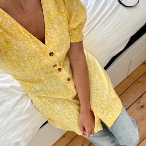 Smuk sommerkjole i flot gul farve med pufærmer. Har et lidt løst fit, så kan passe fra xs-m alt efter hvilket look man ønsker. Brugt en enkelt gang