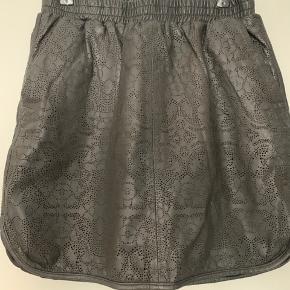 Rigtig fin nederdel med hulmønster i 100% lammeskind. Lommer i siden og elastik i taljen. Brugt to gange.