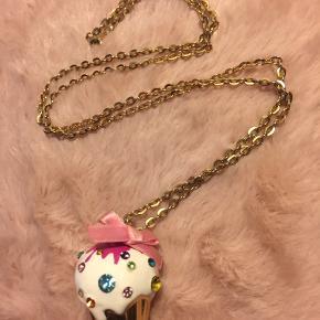 Købt til en del af udklædning, så kun brugt én gang. Guldfarvet halskæde med muffin vedhæng med similisten. Kæden er 70 cm lang, vedhænget er ca. 3 cm højt. Nypris: 150,-