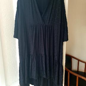 Flot kjole i sort med små prikker. Den går længere ned bag til. Den går mig lige over knæene foran, og jeg er 167 høj. Den er brugt og vasket enkelte gange.