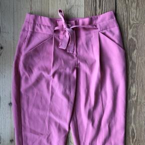 Fine lyserøde løse bukser med bånd. Str L, men passer en S/M. Brugt få gange. Hentes i Århus/Brabrand eller sendes for 38 kr med dao