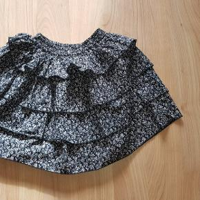 Sød nederdel i sort og grå farver. Der er elastik i taljen.