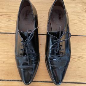 Sorte herreinspirerede sko i shiny skind fra Wonders. Patina foran. Kan ikke undgås pga. materialet. Lidt ridser på indersiden af skoene. Wonders er kendte for at lave pæne, men behagelige sko, og det er de her. 4 cm hæl.