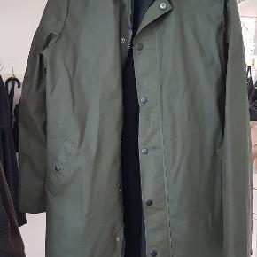 Lækker regnfrakke i Oliven.  Ærmer: 67cm Længde: 88cm BM: 2x54cm Talje: 2x56cm