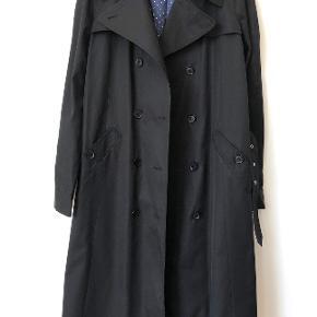 Fin klassisk sort trenchcoat med hvidprikket foer på klar blå baggrund fra Mads Nørgaard. Aldrig brugt. Nypris 2.500 kr. Mål:  Brystvidde, når frakken er knappet: 2x 51 cm Længde fra skulder til bund: 112 cm