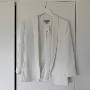 Hvid blazer fra H&M. Stadig med prismærke, derfor aldrig brugt og i pæn stand. Blazeren er dog blevet tabt, så den har en lille plet (se billede).