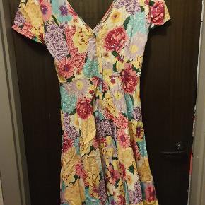 Smuk feminin, 50'er inspireret sommerkjole fra britiske Collectif. Kjolen har en dyb udskæring både foran og bagpå og har swing-skirt som en ægte 50'er diva!