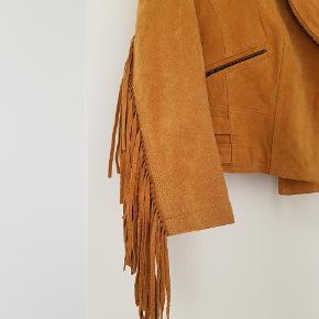 Jakke i ægte læder med kvaster.  I rigtig god stand. Eneste brugsspor er en plet bagpå (se sidste billede), og derfor sælges den billigere.