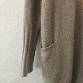 Rigtig dejlig cardigan fra Filippa K. Den er brugt, men det kan ikke ses, da det er rigtig god kvalitet.  Den er 32% uld, 32% alpaca og 30% polymorfe. Den går til omkring knæet og kan lukkes med 2 store knapper  Nypris er 1700 kr. Den er købt i efteråret 18