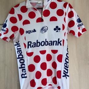 Den røde prikkede cykel bluse Rabobank str s Brystmål ca 2x 43 Hofte ca 2x 39 Længde ca fra skulder og ned61 foran og ca 69 cm bagpå Ærmelængde ca Brugt meget  Materiale100 % polyester