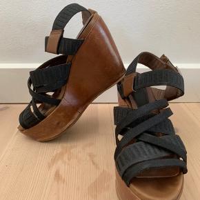 Platform sandal fra Marni, ny pris ca 3000kr. Brun læder platform og brune detaljer, sorte tekstil remme. Nem og behagelig at gå i pga .platformen. Sål er forstærket på hæl, og de små brugsmærker der er i platformens læder, kan dækkes med plejeprodukter (det kan jeg evt gøre inden forsendelse).