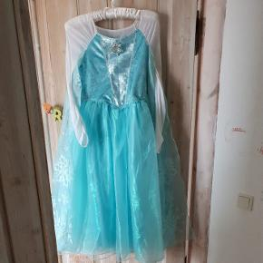 Virkelig flot Elsa udklædningskjole i str 135-145 (passer ca 8 årig). Der er musik/Elsa-sang i broche - virker! Købt i Disney Store for 2 år siden til 700 kr.