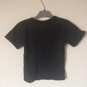 Shango - t-shirt med print Str. 92/98 Næsten som ny Farve: sort Lavet af: 100% cotton Mål: Bredde: 58 cm hele vejen rundt Længde: 35,5 cm Køber betaler Porto!  >ER ÅBEN FOR BUD<  •Se også mine andre annoncer•  BYTTER IKKE!
