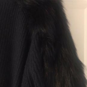 """Sort strik med kunstig """"pels"""" på ærmerne.  Materialet er 54% akryl, 40% polyamid samt 6% uld.  Den er rigtig blød og lækker."""