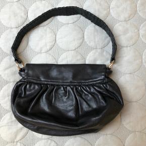 DKNY håndtaske med kort skulderrem. Skjult magnet lukning. Eet stort rum og et mindre rum med lynlås. Meget pæn stand. Super, lækkert sort, blødt skind.