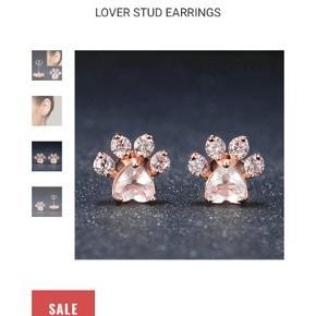 Helt nye øreringe fra Dog Pawty i rosegold farvet med lyserøde sten i. Øreringene er ikke forgyldt men ligner. Jeg mener, at det er kobber.