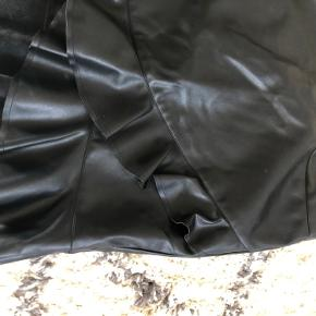 Ny Neo noir nederdel i læder look. Nypris 500kr. Prismærket er klippet af, men har aldrig været brugt.  100% polyester. Materialet er elastisk og den har lynlås i siden.