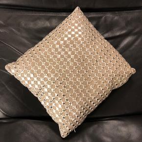 Pude. Støvet rosa-beige med sølvfirkanter, Zenza  Skøn pyntepude fra Zenza. Puden er håndlavet i egypten og er dekoreret med fint mønster på forsiden med sølvfirkanter i centrum af sølvstjerne. Den har en meget smuk bundfarve - sart støvet rosa-beige.  Mærke: Zenza Størrelse: Ca 38 x 38 cm Grundfarve: Beige med en meget lys rosa tone  Mønster: Sølv.  Zenza kombinerer ofte gamle teknikker med et moderne twist i deres design og udvikler en meget elegant, intim men alligevel moderne atmosfære.  Nypris: 45 EUR = ca. 330 kr  Købt i Holland. Ca 2.5 år gammel. Bare ligget som pyntepude. Forsiden fremstår rigtig flot. Bagsiden fået fået nogle pletter (se billede 5 & 6). Sælges derfor til ekstra attraktiv pris.