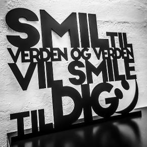 """Skilt udskåret i 2 mm stål og sortlakeret. Tekst: """"Smil til verden og verden vil smile til dig"""".  Skiltet kan ophænges i selve udskæring med 2 sorte søm, som medfølger. Ellers kan skiltet stilles op ad væg, hylde ell. lignende.  Bredde × højde: 41x33 cm. 139 kr. 62x50 cm. 249 kr.  Fragt pris: 29 kr u/omdeling ell. omdeling til erhvervsadresse. 48 kr m/omdeling til privat adresse."""
