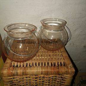 To stk. skønne fyrfadsstager i sart rosa, transparent glas med metalophæng. Brugt, men i pæn stand. Størrelse: ca. 12-13 cm.