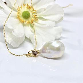 Super smukt vedhæng og elegant tynd sterling sølv halskæde.  Vedhænget er en barok perle i str 18-20 mm.  Den er specielt stor og enhver af disse perler er helt unikke.  Ophænget er et flot forgyldt led med zirkonia sten. Prisen er pr. sæt (kæde og vedhæng)