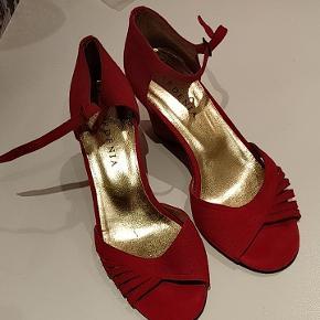 Røde sko med kittenhæl fra Gardenia. Ruskind. Små sorte streger på indersiden (se sidste billede), men man ser det ikke, når man har dem på. Brugt to-tre gange. Meget reel størrelse 37. Højde på hæl 6 cm. Såler er fine, dog med ganske få ubetydelige ridser under forfoden.