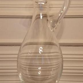 Varetype: Charlotte Amalie Karaffel Størrelse: 42 cm Farve: Glasfarvet Oprindelig købspris: 3495 kr.  Holmegaard - Charlotte Amalie karaffel i mundblæst glas, designet af Per Lütken i 1980.  Det er et stykke fantastisk glaskunst, som kan anvendes som en skulptur i dit hjem.