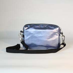 Fin skuldertaske/crossover fra franske Jack Gomme fra Paris. Let og enkelt design. Slidstærkt materiale og smuk blåmetallic farve. 15 x 20 cm.