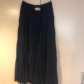 Smukkeste plissé nederdel i mørkeblå. Elastik i taljen så kan passes af 36-40. Kun brugt få gange så stadig rigtig flot!   Mængderabat gives.