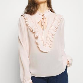 Helt ny fra AW20 Str 36/S  Pleated ladies' blouse in georgette with a frilly collar, tie closure and slit at the neckline. The V-shaped pleated plastron is trimmed with frilly details. The tank top lining provides coverage.