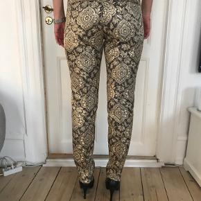Virkelig smukke pressefoldbukser i guld og sort fra Malene Birger. Bukserne har kun været brugt to gange.