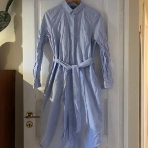 Lidt små i størrelsen, passer bedst S/36 synes jeg. Skjortekjolen har knapper hele vejen ned, bindebælt og 2 lommer.