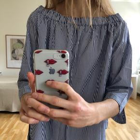 Blå- og hvidstribet skjorte med dyb halsudskæring sælges. Skjorten er en størrelse M, men passes bedst af en S. Den har kun været i brug en enkelt gang, og bærer derfor ingen tegn af slid - den fremstår helt som ny. Køber betaler fragt, hvis varen skal sendes.