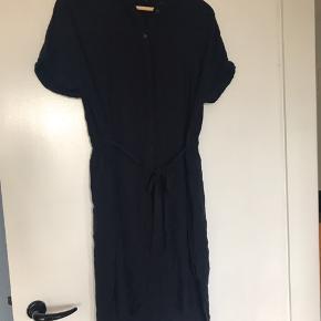 Aldrig brugt, men vasket 1 gang. Mørkeblå kjole med knapper hele vejen ned, og med bånd til taljen.