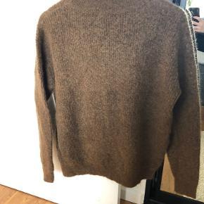 Lækker strik med høj hals. Flot brun farve. Str small, men passer også str medium. Oversize model. Flot mønster i strikken.