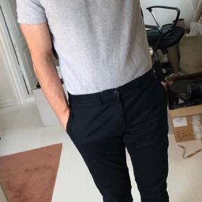 Lysgrå melange pique polo med trykknapper. Perfekt til enten jeans eller et par habitbukser.  OBS! Ønskes handlen gennemført via TS afholder køber gebyret.