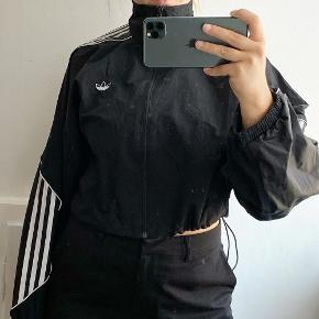 Fed cropped Adidas jakke i vandafvisende materiale. De grønne prikker på billederne er fra en lampe ikke noget der er på jakken. ☺️ Bud modtages !