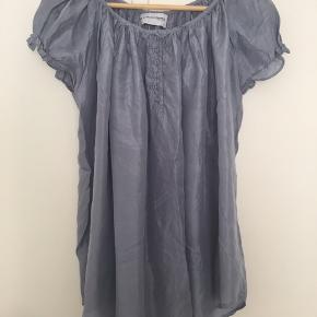 Fin lyseblå bluse i silke. Brugt men pæn, mindre brugsspor i silken. Bred model, kan også passes af str. M.