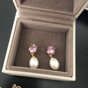 Flotte ørestikker med lilla sten og perler.