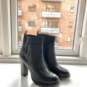 Zara basic collection high heel black leather ankle boots. Rubber track sole, elastic band at the ankle. Approx 10 cm height. Size 38. Perfect condition, never worn - faint scoffs on the heels due to prolonged storage.