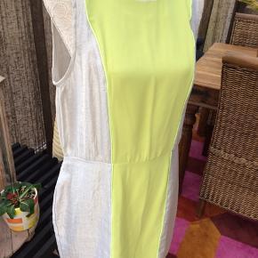 Kjolen har skjult lynlås i siden - den krøller ikke. Farverne er limegrøn og beige/sølv. Ny pris kr 1.299,-. Den er af mærket Millioner & Honey. Købt i Milano.
