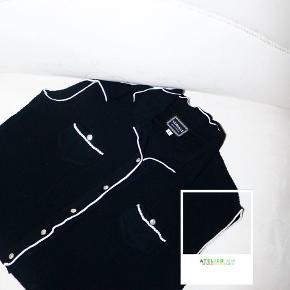 - BENYT 'KØB NU' FUNKTIONEN, VED KØB -  Mørkeblå/sort strikvest fra Versace Jeans Couture. Vesten har sølvfarvet dekorative knapper med logo, påsyet logo nederst foran, små lommer på brystet og gennemgående kontrasthvide kanter. Den er i en fin strik med masser af stretch og kan bruges både åben og knappet.   ○ Mærke: Versace Jeans Couture ○ Størrelse: L (IT - svarende til en dansk str. 38) - Skulderbredde: 36 cm - Brystmål: 40 cm - Taljemål: 39 cm - Længde: 40 cm ○ Fit: Tætsiddende med stretch ○ Stand: Super ○ Fejl/Mangler: Ikke umiddelbart ○ Materiale: 100% Viskose