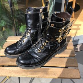 Sorte støvler der egner sig godt til både efterår og vinter. Lidt slid på dem men primært mærker da skoene er i 100% lak læder, med guld detaljer. Skoene er købt i Milano og nypris var omkring 2400kr. Prisen er fast, køber betaler selv porto eller kan afhentes på Nørrebro eller i Brønshøj.