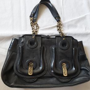 Brugt Fendi-taske (B Bag) sælges billigt. Fenditaske i sort læder med metal- og læderrem samt FF-spænder. Tasken måler ca 23 x 34 cm. Der er lidt brugsspor på tasken, som vist på de sidste billeder - derfor den gode pris.