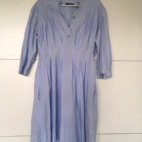 Skjortekjole fra Bruuns Bazar str. 42. Bomuld. Lyseblå og tyndt, let gennemsigtigt stof. Knapper foran og lynlås i siden. Lommer.  Købt brugt, aldrig brugt af mig. I perfekt stand.  BYD. :)