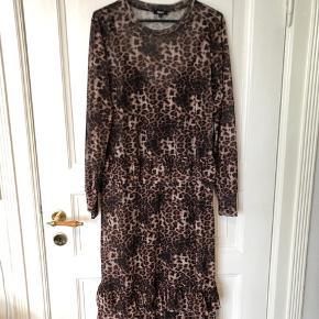 Super fin kjole til både fest og hverdag.  Kjolen er i net (gennemsigtig) derved følger der en sort underkjole med. Der er en flæse øverst på skørtet, og endnu en nederst, som vist på billede. Kommer fra et ikke ryger hjem. Leopard kjolen er 95% polyester/5%elastan Underkjole er i 100%viscose